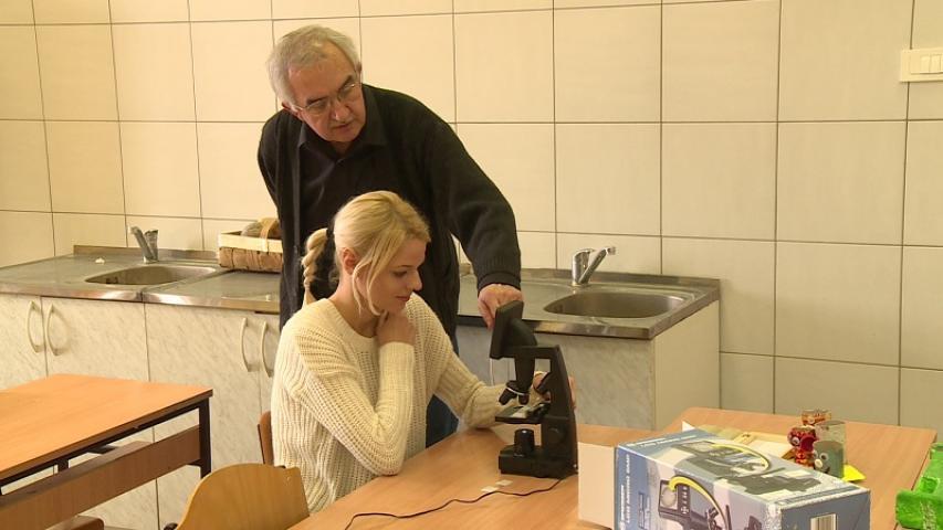 Mikroszkóp használatát magyarázza a tanár